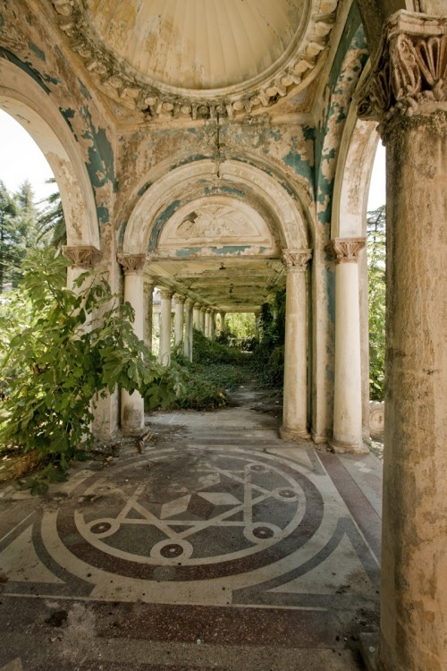 A photo of a walkway in an abandoned railway station. The architecture is ornate but deteriorating, and plants have started to overgrow parts of the structure.