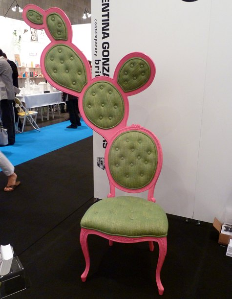 A photo of an ornate chair with a pink frame and green seating that looks like a prickly pear.