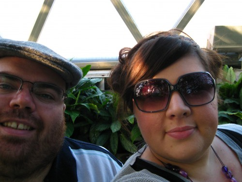 Photo of Natalie (wearing sunglasses) and half of Nick (wearing Pa's flatcap) inside the tropical dome of the Botanic Gardens