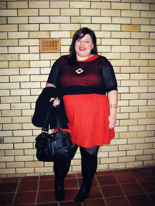 Photo of Natalie wearing a red babydoll dress with a mesh top, and black leggings. A jacket is slung over an arm that also carries a black purse.