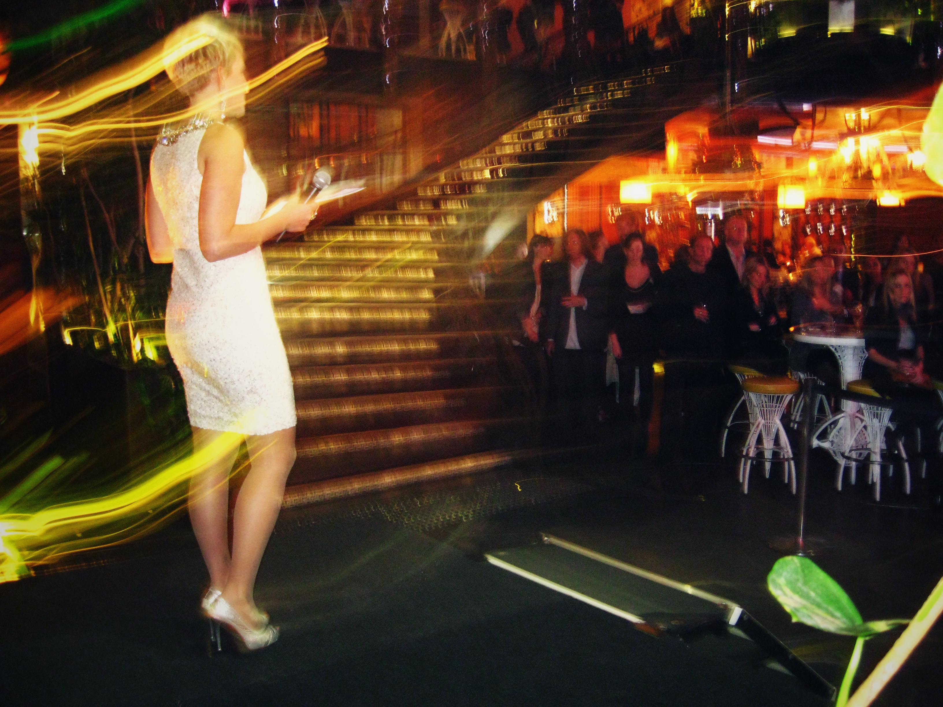 A slim white woman wearing an ivory sequinned dress stands on the stage on the left, the crowd is to the right.