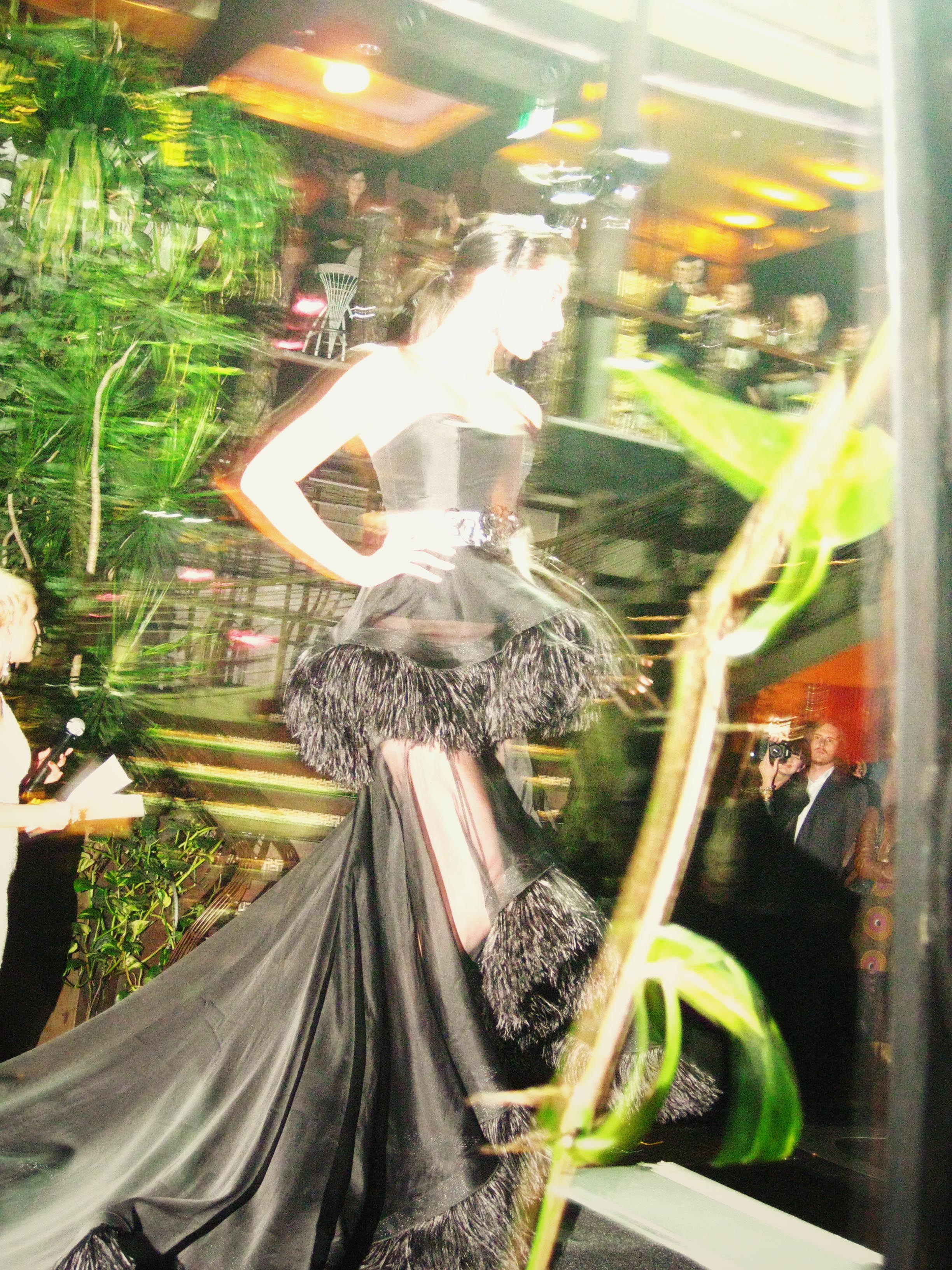 A model wearing a black dress with a frou frou skirt turns around