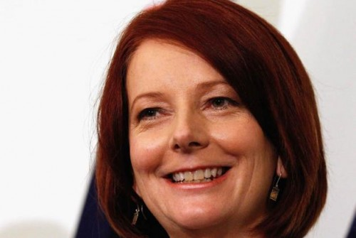 Close up photo of the face of Julia Gillard, 27th Prime Minister of Australia, a white woman with chin length red hair. She is grinning. A small part of the Australian flag is visible behind her.