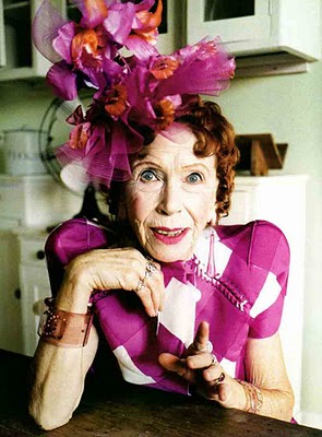A photo of an older woman dressed in fucshia sits in a kitchen, bright pink and orange flowers in her red hair, her right hand brought up under her chin and her left hand gesturing towards the camera.