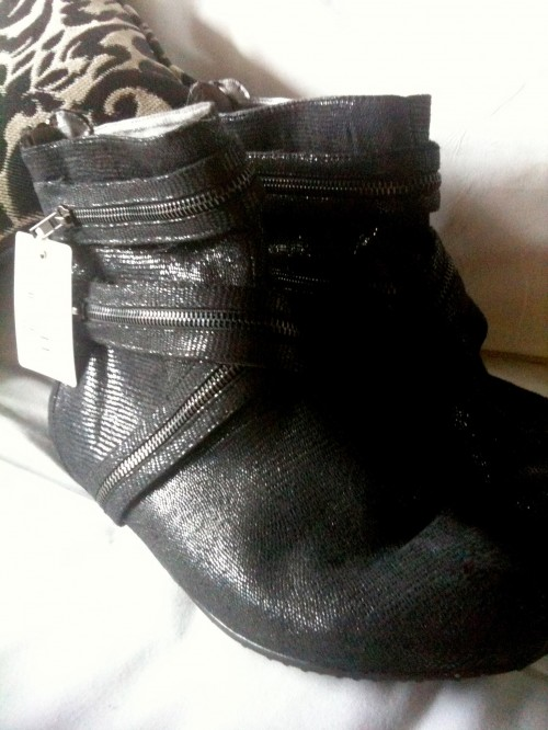 Photo of a pair of black sparkly boots adorned with superfluous zippers.