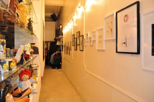 Photo of a wall on the right side of a narrow corridor with framed artworks.