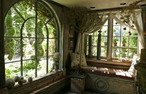 A photo of two adjacent walls with two big old windows with a gorgeous view to a green garden.