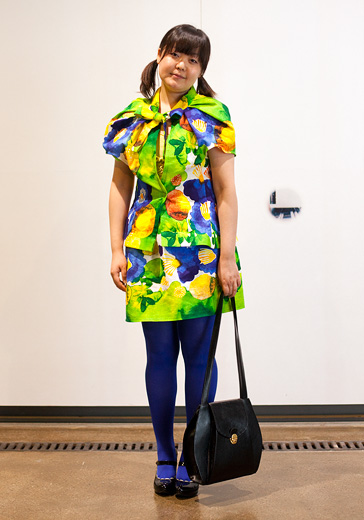 A street style photo of a young woman wearing a brightly printed dress of acid green, yellow, purple and blue wearing blue tights and mary jane style shoes, carrying a big black shoulder bag.