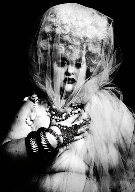 A black and white photo of a pale skinned plus size model wearing a curly blonde wig with tulle pulled over her head. Her hand clutches at the tulle on her chest and she's wearing jewellery draped over her hand with big bangles.