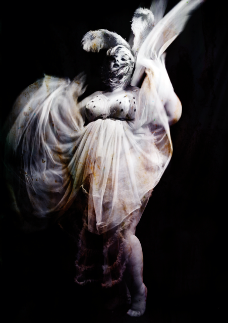A photo of a pale skinned plus size woman in a white tulle-layered dress on a black background.