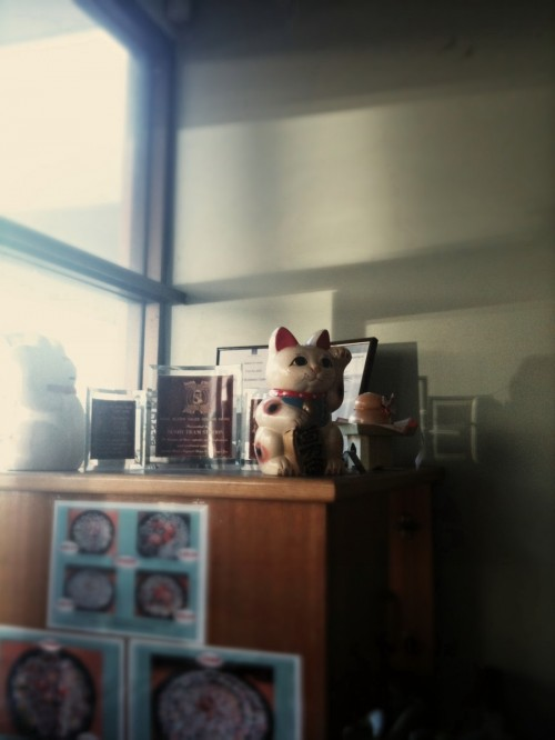 Waving cat in a sushi restaurant on top of a cabinet with certificates and a menu taped to the front of it.
