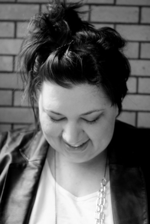 A black and white, head and shoulders, photo of me. I'm looking down, my hair is up, and I'm wearing a leather-look jacket with a white tshirt and a big chain necklace.