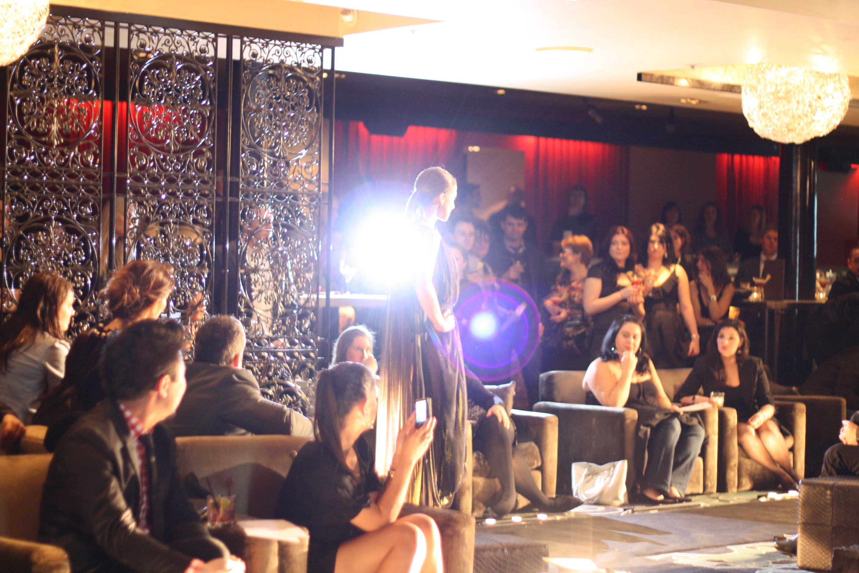 Model walking down a runway amongst a crowd of people with camera flashes popping around her.