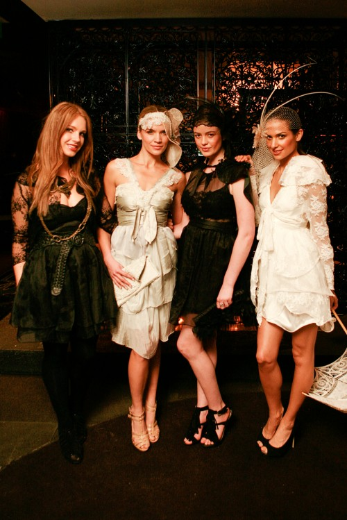 Designer Anna Campbell stands with three models, all wearing black or white variations on lace, layered feminine dresses.