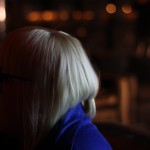 A blonde woman is on the left with out of focus ambient light to her right.