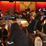 A crowded bar with low grey/ fawn couches with a long bar in the background. Behind the bar is red curtains and a pair of antlers on the wall.