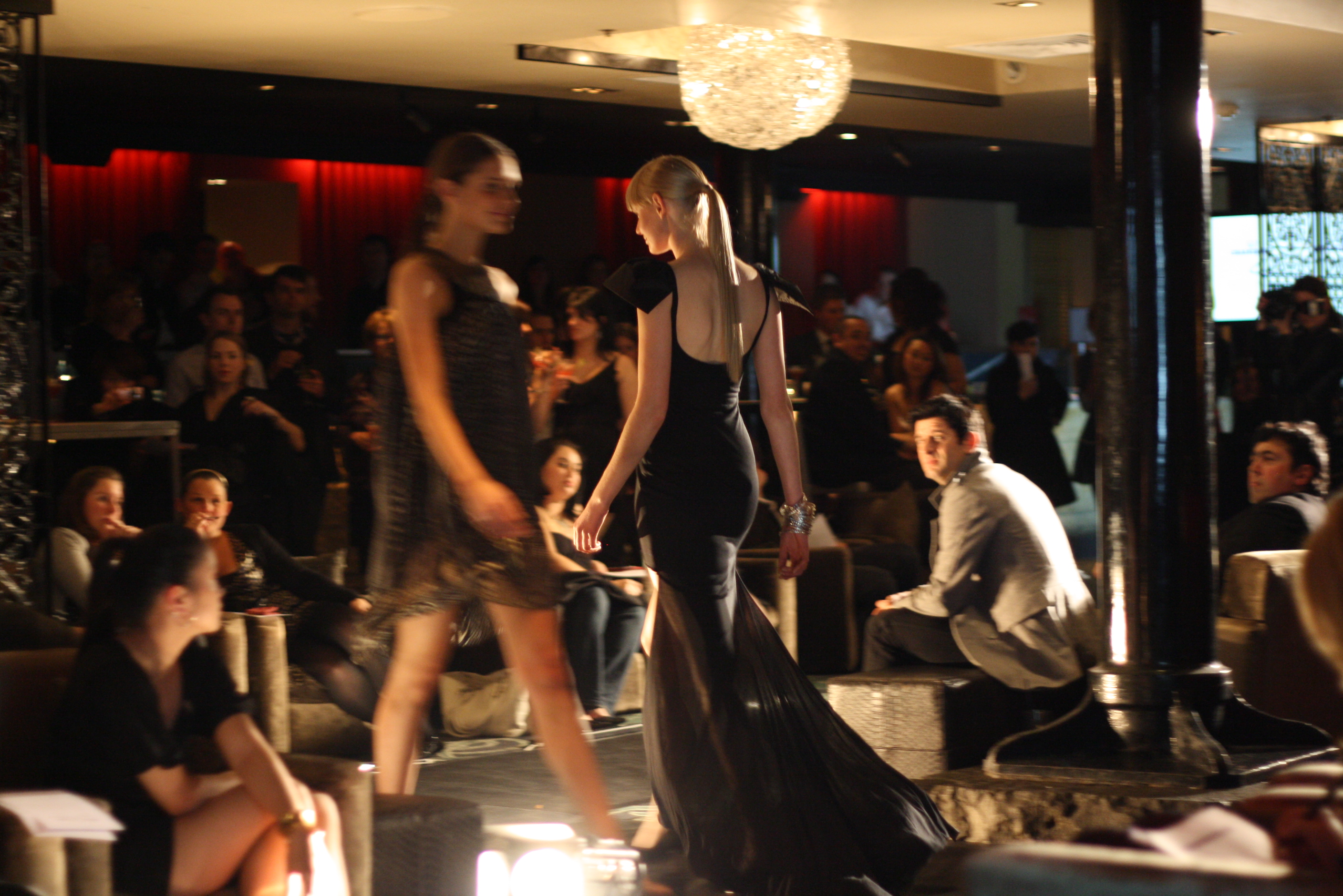 Two models pass each other on the runway, the model in focus is wearing a black sleeveless tight dress with a flowing black mesh train.
