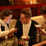 A woman on her phone, a man holding a martini and another woman holding a martini chat.
