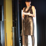 A woman stands behind a microphone reading from prompt cards. She wears a black leather dress, black leggings and black sandals.