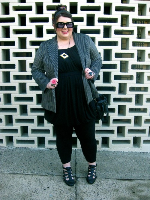 A photograph of Natalie against a decorative brick wall. She wears a black bubble dress over black leggings with a gold/black pin striped blazer and sandal boots with buckles up the front.