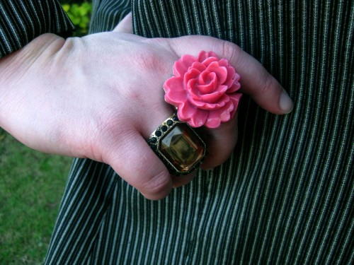 Photograph of Natalie's right hand, she wears two large rings: one a 3D pink flower, the other an amber rectangular gem.