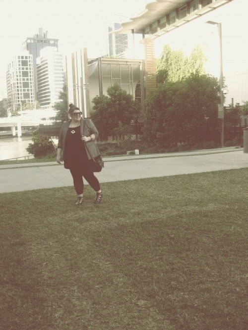 An overly edited photograph of Natalie on the GoMA Brisbane lawn, the river and CBD in the background.