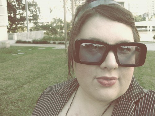An overly edited photo of Natalie wearing a pair of sunglasses with heavy black squarish frames.