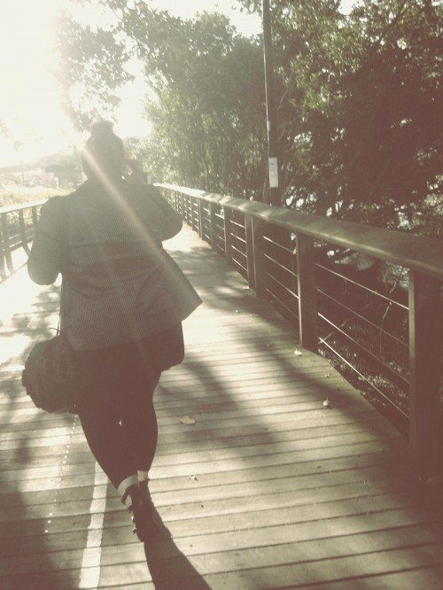 An overly edited photo of Natalie walking away down a wooden walkway, a sunflare blowing out most of the top third of the picture.
