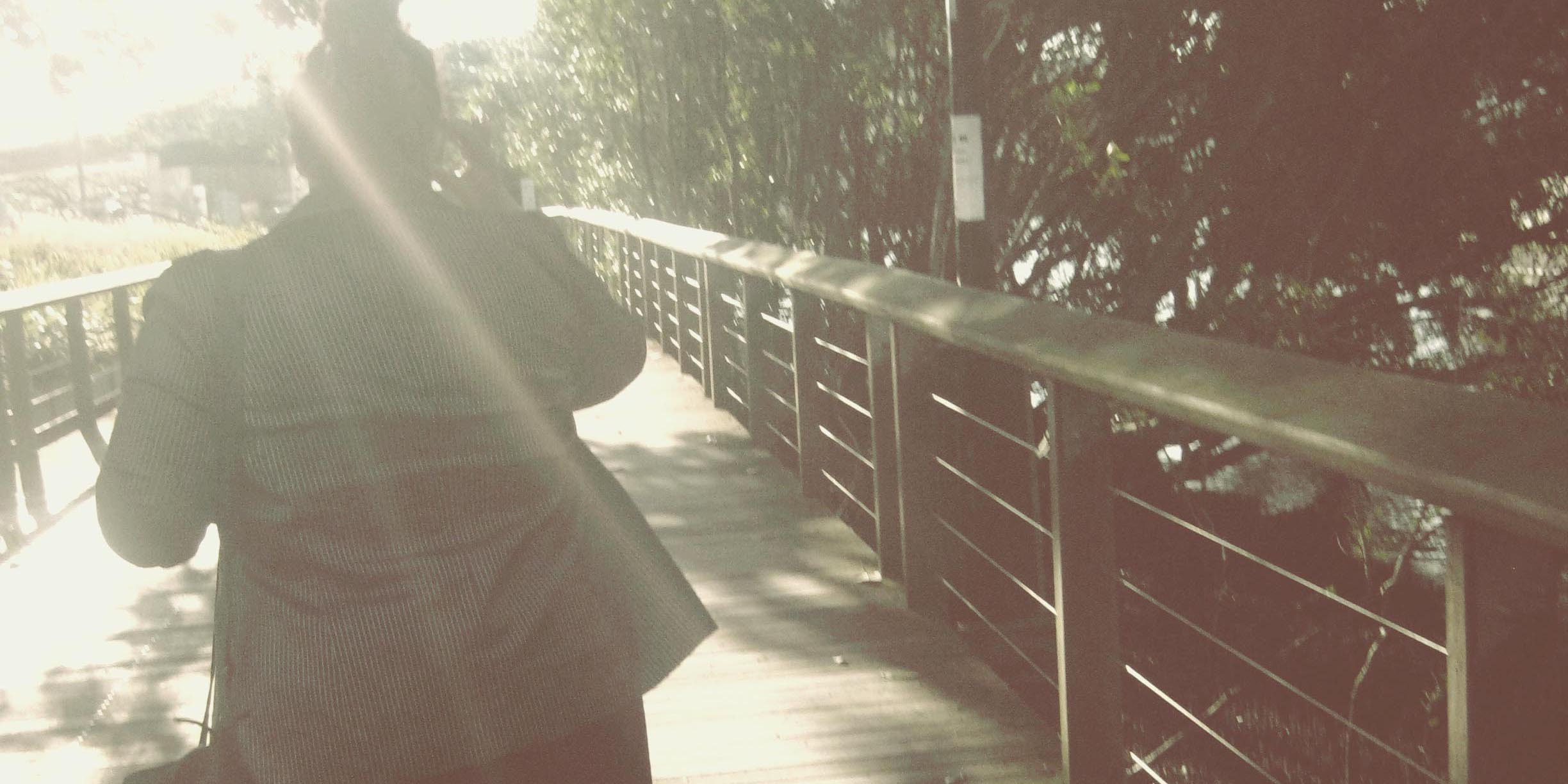 Photo of Natalie's silhouette, she's walking away from the camera along a wooden walkway into a solar flare.