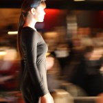 The profile of a model in a black dress walking.