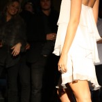 Back of model wearing a white tiered dress in a floaty fabric.