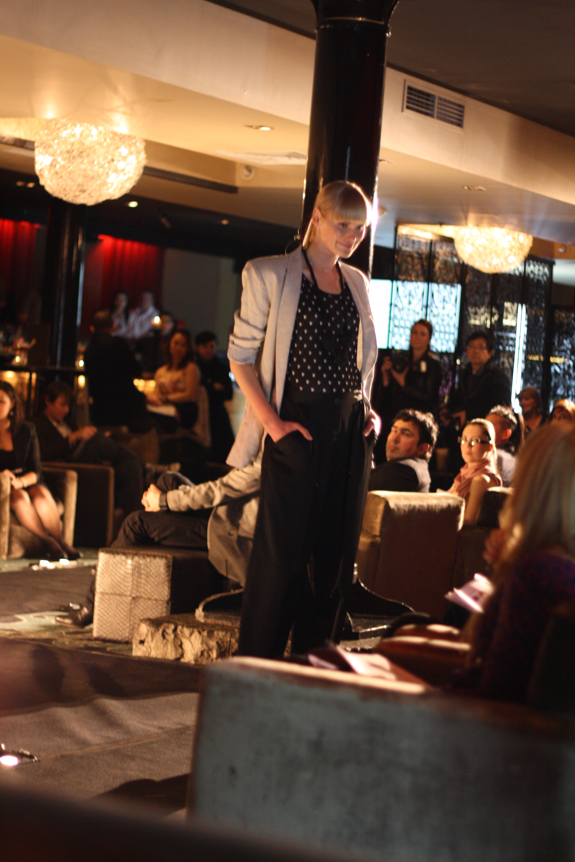 A model poses for the judges in masculine tailoring, with a light blazer and dark top and pants.