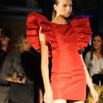 Model wearing a red dress with wide and spectacular ruffled sleeves.