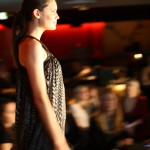Profile of a model walking down the runway in a floaty dress in a dark small pattern.