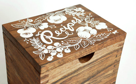"A small wooden recipe card box with a white screenprinted floral design on the lid and handwritten lettering saying ""Recipes""."