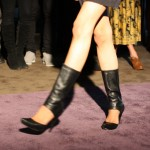Model walking down runway in shoes that feature a mid-calf height leather cuff and simple court shoe.