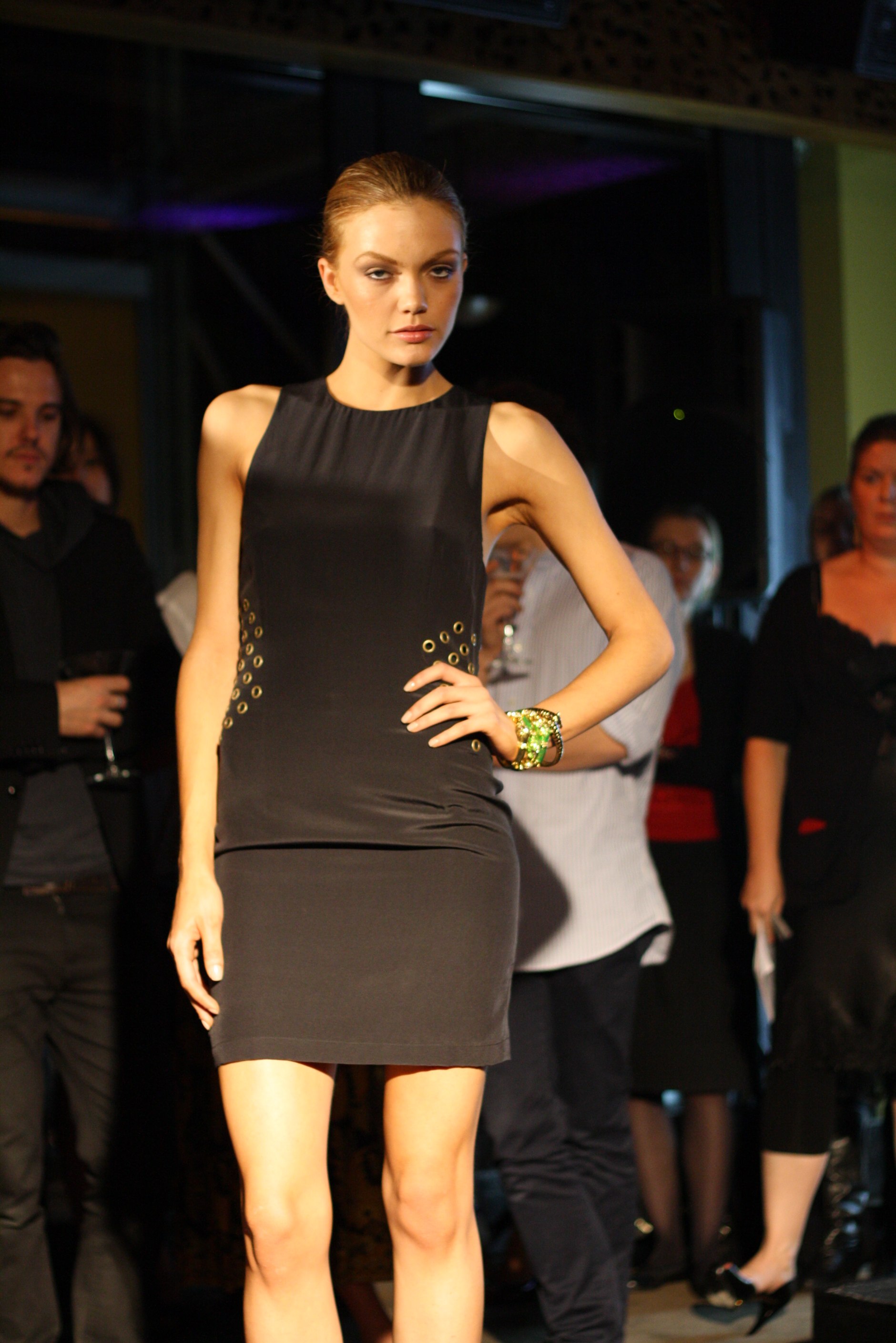 Model wearing a simple black sheath dress with brass rivet-like details at each side of the waist.