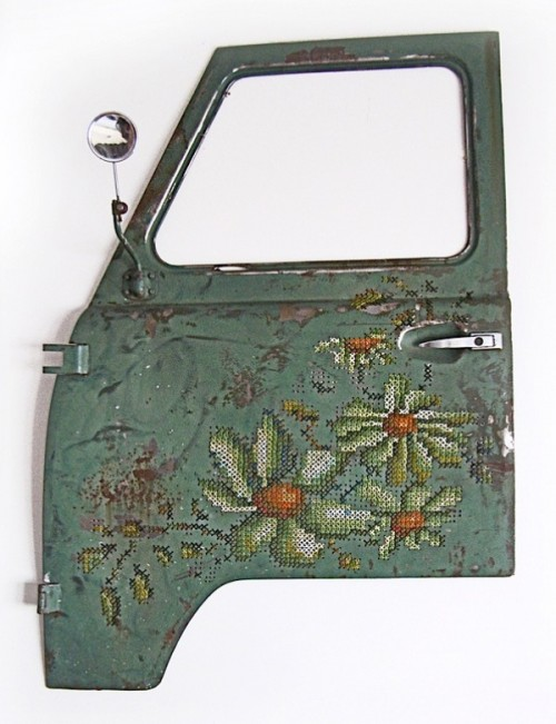 The door of a truck, teal in colour but rusted, has been embellished with large cross stitched flowers.