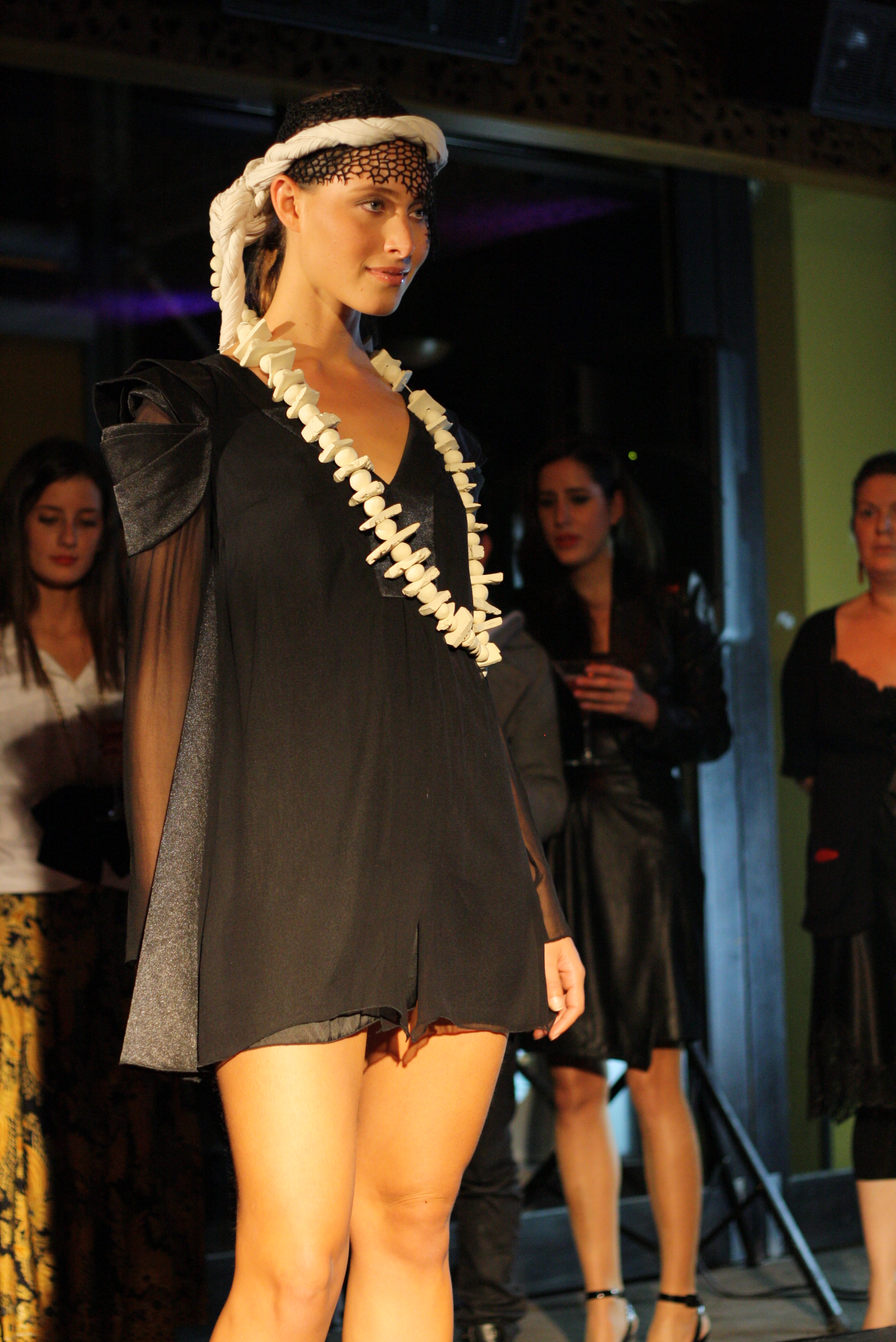 Model wearing a black and grey dress with a necklace that looks like vertibrae!