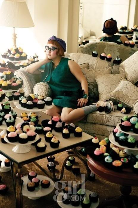 A young woman sits on a couch, surrounded by hundreds of brightly frosted cupcakes.