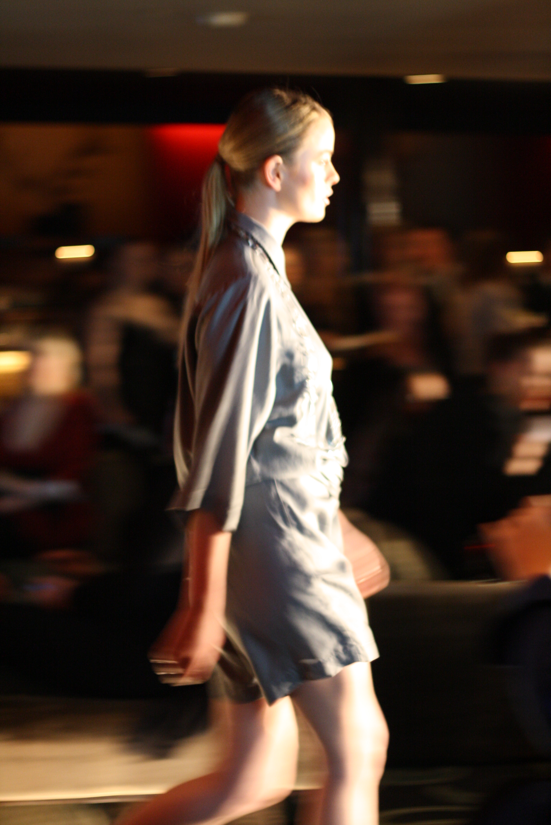 Side profile of a model walking in a grey romper-style design - with bracelet length sleeves and short shorts.