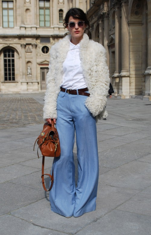 A young slim pale skinned woman wearing a white buttoned up shirt with blue flared jeans and a brown belt. Over the outfit she wears a white fur (looks faux!) jacket, and she carries a tan leather bag.