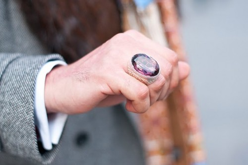 A close up of a man's hand wearing a spectacularly huge purply coloured gem ring.