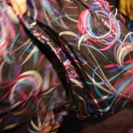 Detail of model's skirt billowing behind her. The fabric features a large pink, white and cyan circular pattern.