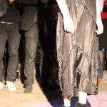 Model wearing a long sheer black dress with diagonal seams and detailing.