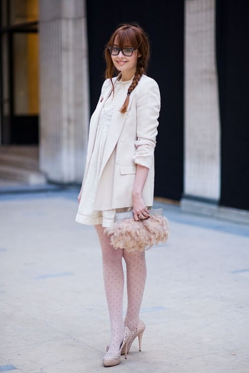 A street fashion photo of a young, slender, pale skinned woman wearing a cream dress and blazer, textured tights and cream heels holding a pale pink feathered clutch purse.