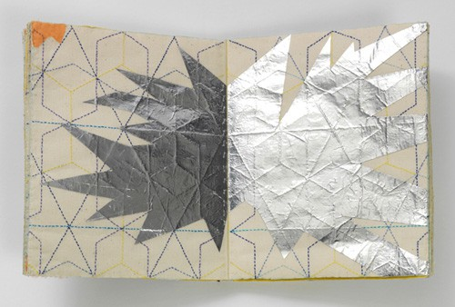An open book, the spread embroidered with a geometrical pattern and an explosion-like graphic has been laid over the top, perhaps in silver leaf?