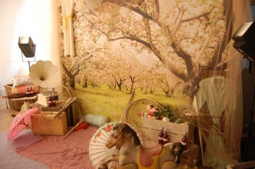 A photo of a room with a giant picture of a cherry blossom tree (I think!) on the wall and lots of whimsical things strewn about on the floor including: parasols, rocking horses, old suitcases and an old-fashioned record player with a trumpet device (can't remember the name of this!)