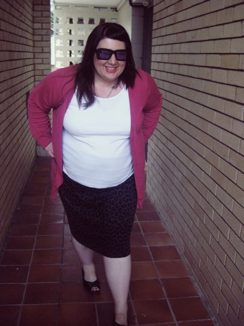 Outfit photo of me wearing a white tank top with a black/ grey animal print pencil skirt and a pink cardigan. I'm walking towards the camera with my hands on my hips, smiling.