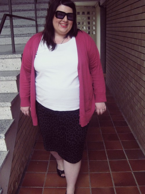 Outfit photo of me wearing a white tank top with a black/ grey animal print pencil skirt and a pink cardigan.